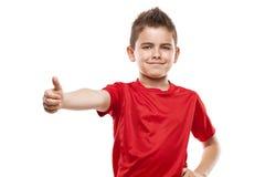 Det stående barnet kyler pojken som gör tummar-upp royaltyfri fotografi