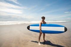 Det starka barnet surfar manståenden på stranden med en surfingbräda. Lodisar Royaltyfria Foton