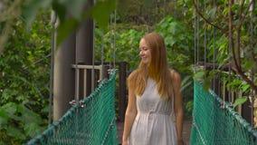 Det Steadicam skottet av en ung kvinna som går på den hängande upphängningbron i Ecoen, parkerar i den Kuala Lumpur staden lager videofilmer