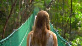 Det Steadicam skottet av en ung kvinna som går på den hängande upphängningbron i Ecoen, parkerar i den Kuala Lumpur staden stock video