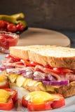 Det stekte ägget stekte i skiva av röd söt peppar och smörgåsen med skinka och säsongsbetonade grönsaker på den vita plattan Matf arkivbilder