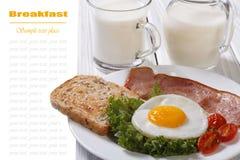 Det stekte ägget med skinka, tomater och nya mjölkar Arkivfoton
