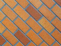 Det stenlade tegelstenbakgrundsfotografiet, glasad brunt på diagonal lutar Arkivfoton