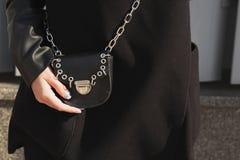 Det stilfulla klädda barnet modellerar i det svarta laget som rymmer liten svartpu Royaltyfria Bilder