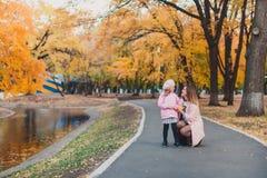 Det stilfulla laget för rosa färger för mohter- och barnflicka 5-6 åriga bärande moderiktiga i höst parkerar Flickan är iklädd en royaltyfri bild