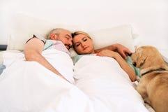 Det stiliga paret i säng sover tillsammans i anslutning med hunden arkivfoto