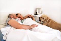 Det stiliga paret i säng sover tillsammans i anslutning med hunden fotografering för bildbyråer