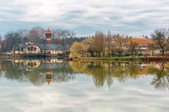 Det stillsamma landskapet med sjön, hus, molnig himmel och träd reflekterade symmetrically i vattnet Nyiregyhaza Ungern royaltyfria foton