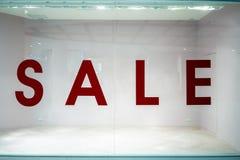 Det stora försäljningstecknet shoppar på fönstret i varuhus arkivfoto