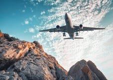 Det stora flygplanet flyger över vaggar på solnedgången i sommar arkivfoton