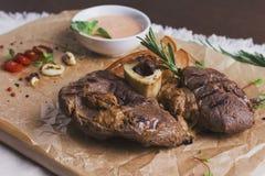 Det stora grillade stycket av kött på benet med sås och kryddor Royaltyfria Bilder