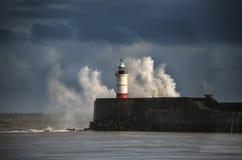 Det stora havet vinkar att krascha över fyren under storm med beaut arkivfoton