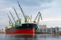Det stora industriella skeppet med kranar laddar i port Arkivbild