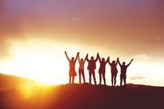 Det stora lyftte lycklig folkets för gruppen framgång för konturer händer royaltyfri foto