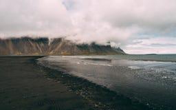 Det stora molnet täckte vestrahorn på stokksnes i Island svart pittoresk sandstrand ingen touristic fläck för folk Fotografering för Bildbyråer