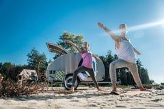 Det sunda flickvän- och pojkvänanseendet i krigare poserar att göra yoga arkivfoto