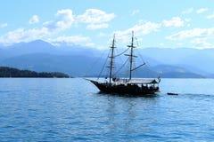 Det svarta fartyget seglar på havet royaltyfri bild