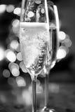 Det svartvita fotoet av champagne hällde in i exponeringsglas Arkivbilder