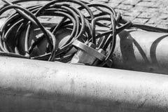 Det svartvita fotoet av industriella slangar med trådar är slutet arkivfoto