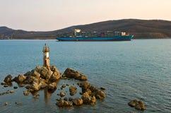 Det Svend Maersk behållareskeppet passerar en liten fyr på solnedgången Nakhodka fjärd Östligt (Japan) hav 19 04 2014 Arkivbilder