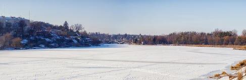 Det sydliga felet för djupfryst och snöig flod och och i avståndet en bro och en tempel av välsignade Xenia av Peterburg Arkivbilder