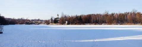 Det sydliga felet för djupfryst och snöig flod och och i avståndet en bro och en tempel av välsignade Xenia av Peterburg Arkivfoto
