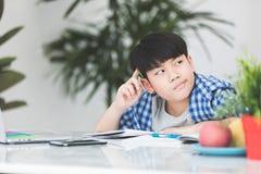 Det tänkande barnet borrade och matade upp att göra hans läxa Royaltyfria Foton
