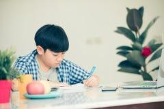 Det tänkande barnet borrade och matade upp att göra hans läxa Arkivbild