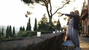 Det talande paret står på trädgården i aftonljus stock video