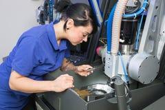 Teknikeren i ett tand- labbarbete på en borrande eller malning bearbetar med maskin arkivfoton