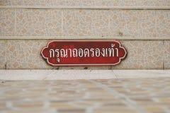 Det thailändska alfabetet, behar tar av dina skor Arkivfoton