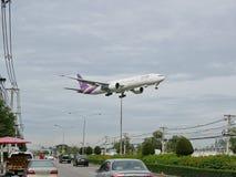 Det thailändska flygbolagflygplanet landar på Chiang Mai International Airport, Chiang Mai, Thailand som lågt flyger ovanför gata Arkivfoto
