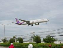 Det thailändska flygbolagflygplanet landar på Chiang Mai International Airport, Chiang Mai, Thailand som lågt flyger ovanför gata Royaltyfri Fotografi