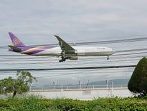 Det thailändska flygbolagflygplanet landar på Chiang Mai International Airport, Chiang Mai, Thailand som lågt flyger ovanför gata Royaltyfria Foton