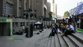 Det thailändska folket sitter och väntar lyssnar lek för musikkonsertmusikbandet i Bangkok, Thailand lager videofilmer