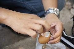 Det thailändska manfolket som skalar skalet, kokade ägg onsen i varm vår för PA Tueng på Mae Chan i Chiang Rai, Thailand arkivbilder