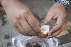 Det thailändska manfolket som skalar skalet, kokade ägg onsen i varm vår för PA Tueng på Mae Chan i Chiang Rai, Thailand royaltyfri bild