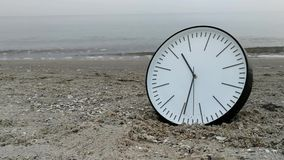 Det Tid begreppet, klocka på sandstranden, bakgrund som går par, lägger benen på ryggen havshorisonten stock video