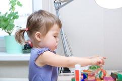 Det tidiga hjärnutvecklingsbegreppet - behandla som ett barn flickan som spelar med papper royaltyfri fotografi