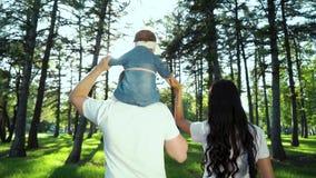 Det tillbaka skottet av den traditionella familjen med behandla som ett barn dottern som går i soligt, parkerar arkivfilmer