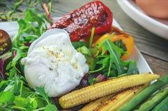 Det tjuvjagade ägget med havregrönsaker, grillad peppar, spenat, arugula, haricot vert och behandla som ett barn sallad close upp arkivfoton