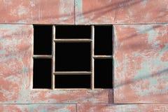 Det tomma fönstret med raster på en metallstruktur målade rött Royaltyfri Bild