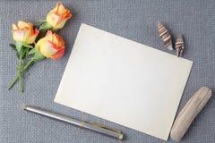 Det tomma gamla hälsningkortet med apelsinrosen blommar arkivbild