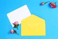 Det tomma hälsningkortet med den gula kuvert- och rosa färgrosen blommar på blå bakgrund royaltyfria foton