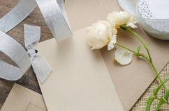 Det tomma inbjudankortet med det bruna kuvertet och steg blommor på wo Arkivfoto