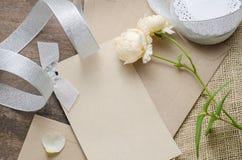 Det tomma inbjudankortet med det bruna kuvertet och steg blommor på wo Royaltyfri Fotografi