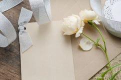 Det tomma inbjudankortet med det bruna kuvertet och steg blommor på wo Arkivfoton