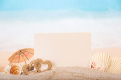 Det tomma kortet med havet beskjuter, hjärtor i sand på stranden Arkivfoton