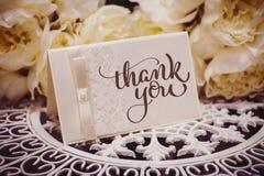 Det tomma kortet som förlägger text som omges av blommor med text, tackar dig Attraktion för kalligrafibokstäverhand Arkivbilder