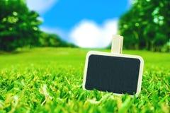 Det tomma svart tavlagemet på fält för grönt gräs med suddighet parkerar backgr Royaltyfria Bilder